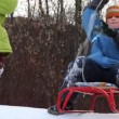 Boy with sled ride down mountain, and then girl behind him — Stock Video