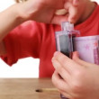 Little girl shows focus transforming euros into dollars — Stock Video #29836853