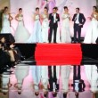Models in white wedding dresses with leading show stand on stage — Stock Video