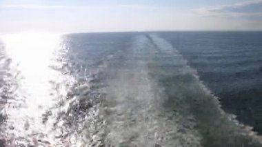 Sun road and track left by ship on water surface, view from deck, time lapse — Stock Video