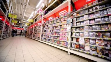 Showcase with dvd discs with varius films in hypermarket Auchan — Stok video
