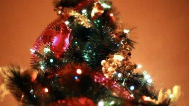 Vánoční stromeček svítí barevná světla na pozadí zdi v místnosti — Stock video