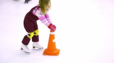 Little girl skates on ice rink helps herself by holding props — Stock Video