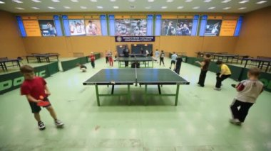 Children go round tables for table tennis and juggle ball about racket — Stock Video