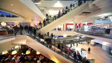 Muitas pessoas se mover em escadas rolantes no átrio de centro comercial de andares múltiplos — Vídeo Stock