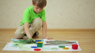 Boy draws color paints with his palm and fingers on sheet — 图库视频影像