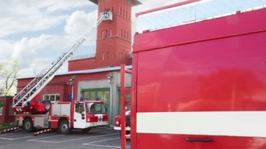 Fire station, two red fire truck with long ladder and a part of another one closer — Stock Video
