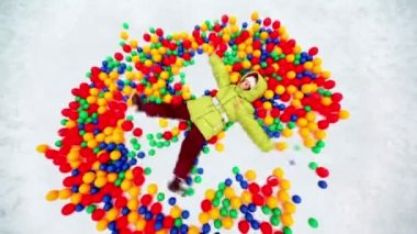 Little girl lying in pile of colored balls in snow hollow — Stock Video