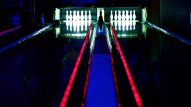 Two bowling lanes lit in dark club, bolls roll and beat tenpins — Stock Video