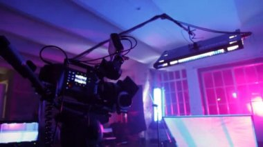 Professional videocamera with display, lamp and reflecting screen in dark room — Stock Video