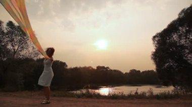 Femme proche lac promenades avec châle flottant sur l'énergie éolienne — Vidéo