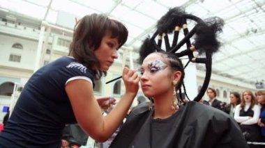 Visagiste maakt make-up voor model met punk kapsel op xvii internationale festival wereld van schoonheid 2010 — Stockvideo