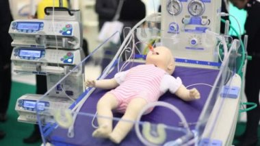 Dummy of little child with tube from suction unit in mouth at medical box on medical exhibition — Stock Video