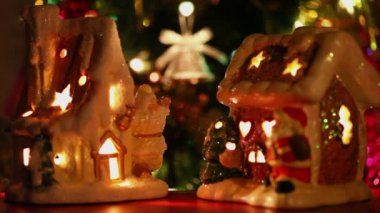 Toy house-candlestick stand at background of christmas tree ornaments — Stock Video