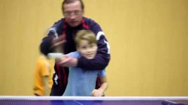Coach stands behind, holds boy and teachs him how to play table tennis — Stock Video