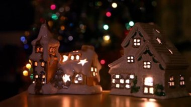 Two toy house-candlestick stand at background of christmas tree ornaments — Stock Video