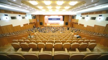 Many people sit in large hall with wooden chairs at conference — Stock Video