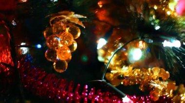 Speelgoed in de vorm van glas druiven opknoping op kerstboom onder gloeiende slingers — Stockvideo