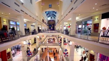 As pessoas andam ao longo de boutiques no átrio de centro comercial de andares múltiplos — Vídeo Stock