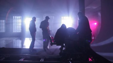 Film crew adjusts equipment on rail cart in dark room — Stock Video