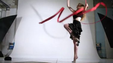 Girl gymnast with ribbon poses for photographer in studio — Stock Video