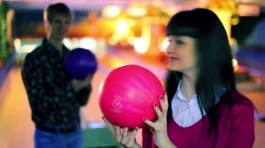 Boy and girl hold bowling balls and smile, and then make strike — Stock Video