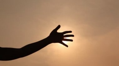 Hand silhouette passes sun beams through fingers against the sky — Stock Video
