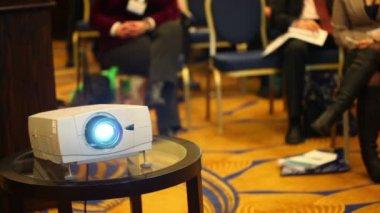 Projektorer på bakgrund av oskärpa sitter personer i konferenssalen — Stockvideo