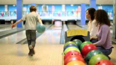 Parents sit and watch little boy throws bowling ball to beat skittles — Stock Video