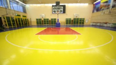 Inside lighted school gym hall with red yellow floor and basket, upward motion — Stock Video