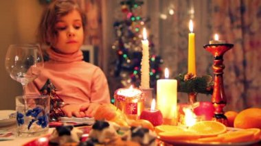 Girl sits at decorated christmas dining table with fruit, candy, candles — Stock Video