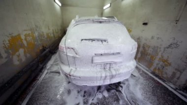 Automobile stand in soap suds inside narrow car wash garage — Stock Video