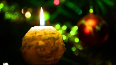 Candle lit in front of festive lights Christmas tree — Stock Video