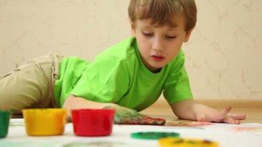 少年は床に横たわっていたし、彼の手のひらでの色の塗料を描画します。 — ストックビデオ