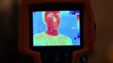 Hand hold thermal image camera, on-screen human face — Stock Video