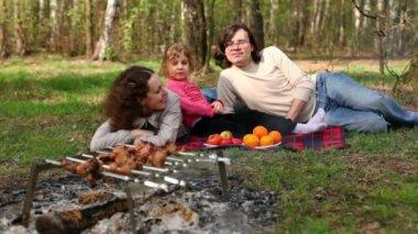フルーツ プレートが近くにいる両親と娘レイ格子縞で覆われて草の上、 — ストックビデオ