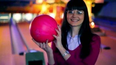 Девушка боулинг мяч и улыбкой, а затем бросает его бить кегли — Стоковое видео