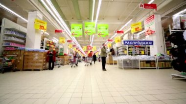 People walk at hypermarket Auchan in trade center Troika — Стоковое видео