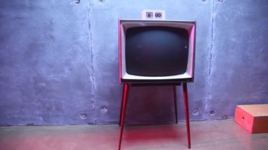 Old-fashioned TV and hours on it stand about block wall — Stockvideo