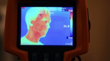 Hand hold thermal image camera, on-screen human face, hand, man opens mouth — Stock Video