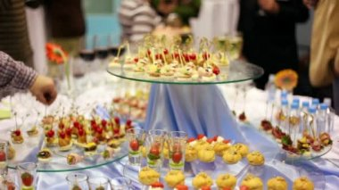 Hands take canapes from appetizer table with wine and other delights — Stock Video