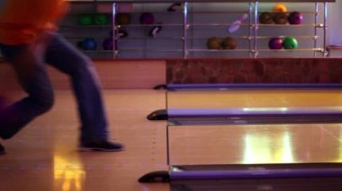 Two men throw bowling ball one by one on parallel lanes in club — Stock Video