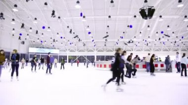 Lot of people skate on large light indoor ice rink in shopping center European — Stock Video