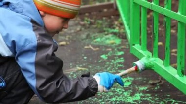 Little boy with paintbrush in hand carefully dye fence on community work day — Stock Video