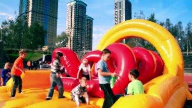 Kids jump on inflated playground at stadium Yantar — Stock Video