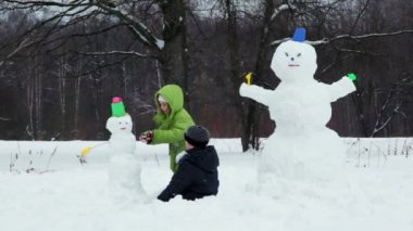 Brother and sister sculpt snowman in park at winter — Stock Video