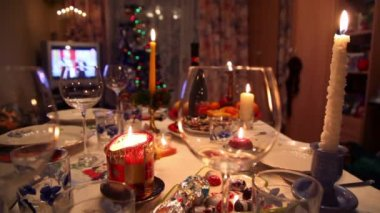 Room with decorated christmas dining table with bottle, glasses, candy, candles — Stock Video