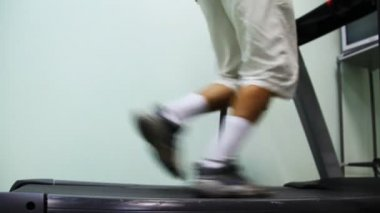Ben man springa på löpband nära väggen i gym — Stockvideo