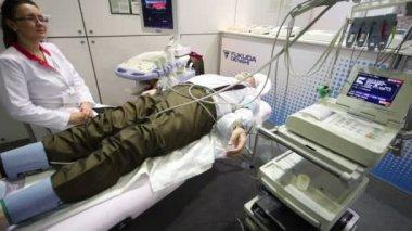Verpleegkundige zit in de buurt van oudere man liggend op bed onder medische apparatuur op medische tentoonstelling — Stockvideo