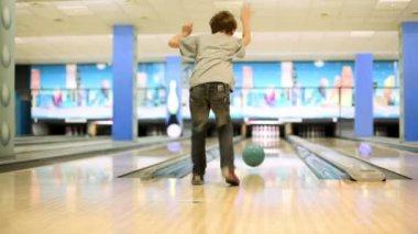 小男孩抛出打败吃喝玩乐、 查看从后面的保龄球 — 图库视频影像
